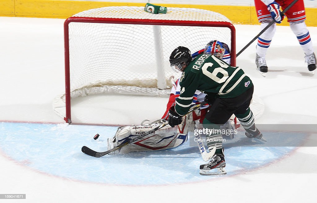 Ryan Rupert #64 of the London Knights slips a puck past Franky Palazzese #32 of the Kitchener Rangers in an OHL game on January 5, 2013 at the Budweiser Gardens in London, Canada. The Knights defeated the Rangers 3-2.