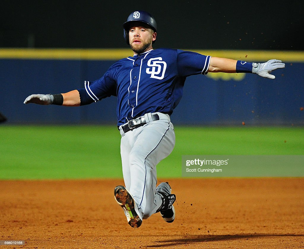 Ryan Schimpf of the San Diego Padres slides in to third base for a ninth inning triple against the Atlanta Braves at Turner Field on August 30 2016...