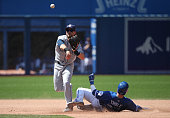 Ryan Schimpf of the San Diego Padres turns a double play in the seventh inning during MLB game action as Josh Thole of the Toronto Blue Jays slides...