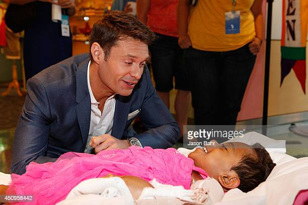Ryan Seacrest shares a moment with a patient during the grand opening of Seacrest Studios at Children's Hospital Colorado on June 20 2014 in Aurora...