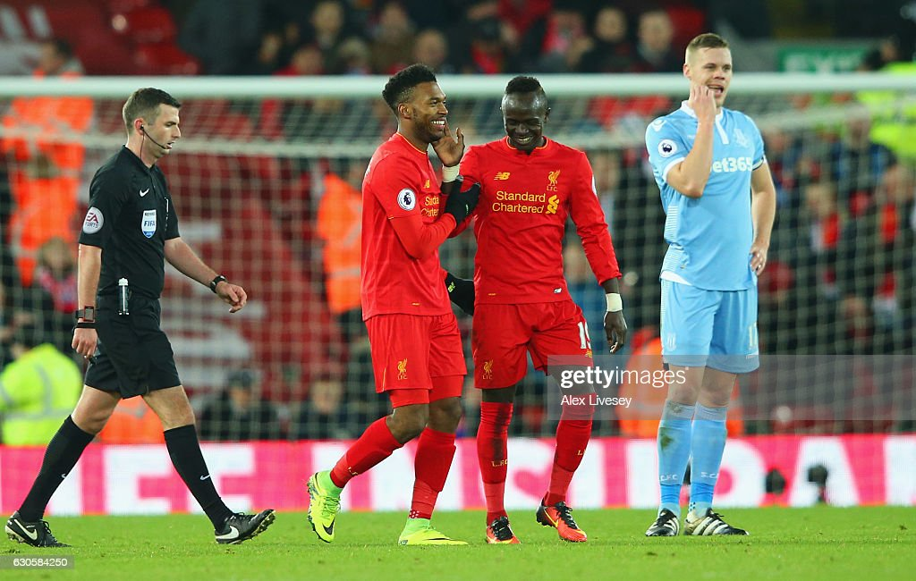 Ryan Shawcross of Stoke City (R) looks dejected as Daniel Sturridge of Liverpool (2L) celebrates with team mates Sadio Mane as he scores their fourth goal during the Premier League match between Liverpool and Stoke City at Anfield on December 27, 2016 in Liverpool, England.