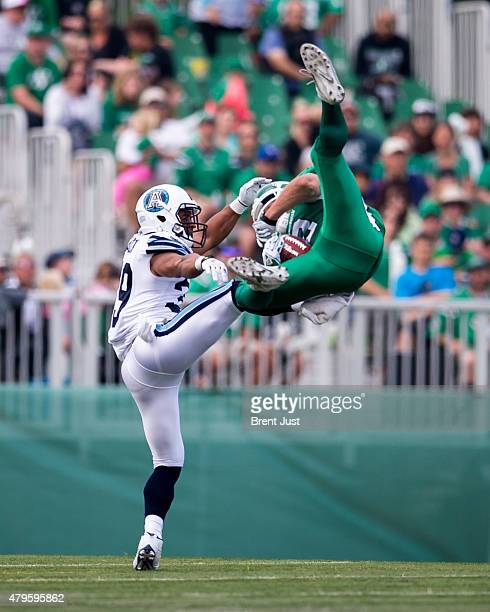 Ryan Smith of the Saskatchewan Roughriders goes up to make a spectacular catch in front of Matt Black of the Toronto Argonauts in the game between...