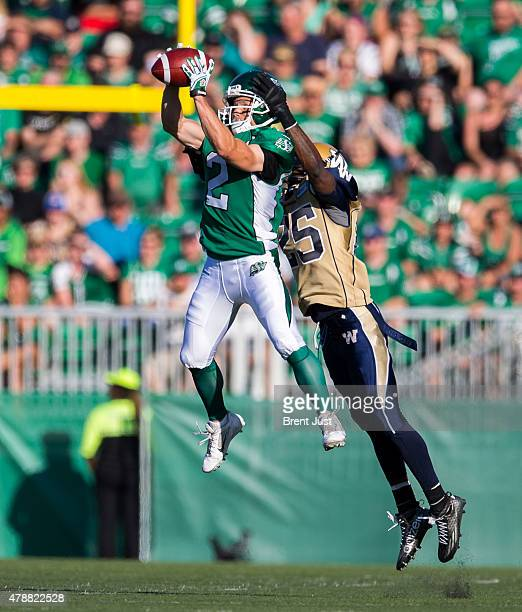 Ryan Smith of the Saskatchewan Roughriders makes a catch in front of Bruce Johnson of the Winnipeg Blue Bombers in first half action in a game...