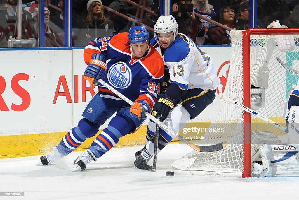 Ryan Smyth #94 of the Edmonton Oilers battles for the puck against Carlo Colaiacovo #13 of the St. Louis Blues on December 21, 2013 at Rexall Place in Edmonton, Alberta, Canada.