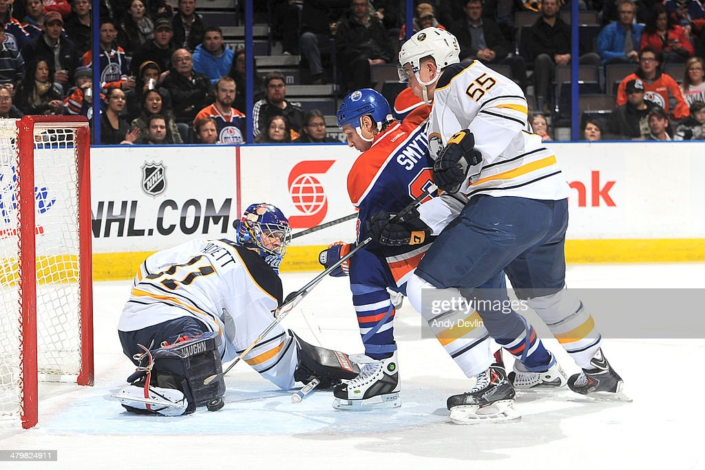 Ryan Smyth #94 of the Edmonton Oilers battles for the puck against Rasmus Ristolainen #55 and Matt Hackett #31 of the Buffalo Sabres on March 20, 2014 at Rexall Place in Edmonton, Alberta, Canada.