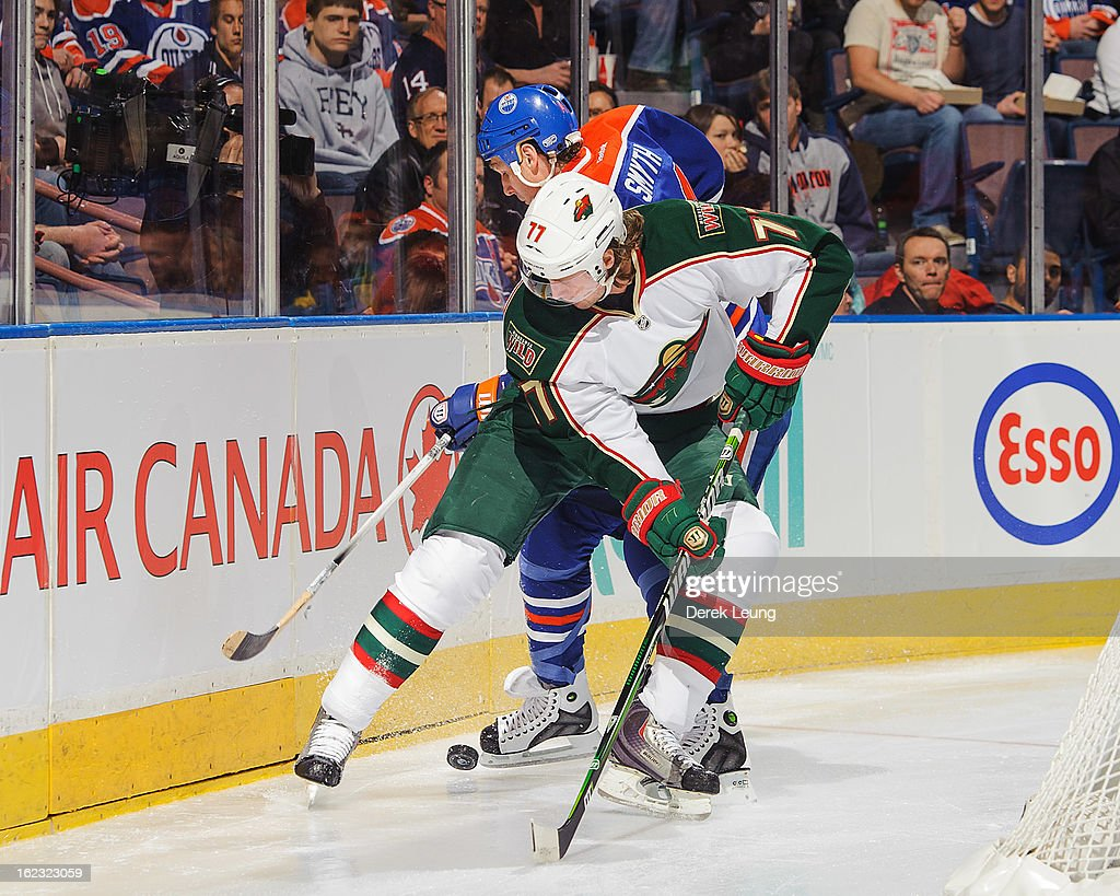 Ryan Smyth #94 of the Edmonton Oilers battles for the puck against Tom Gilbert #77 of the Minnesota Wild during an NHL game at Rexall Place on February 21, 2013 in Edmonton, Alberta, Canada.