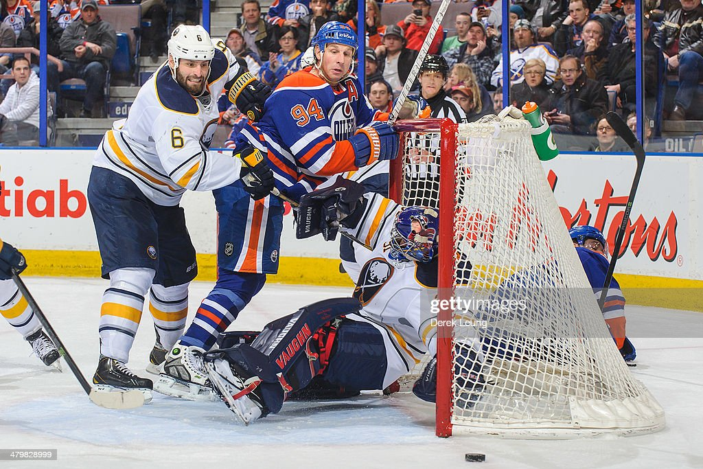 Ryan Smyth #94 of the Edmonton Oilers eyes the loose puck as Mike Weber #6 and goalie Matt Hackett #31 of the Buffalo Sabres defend during an NHL game at Rexall Place on March 20, 2014 in Edmonton, Alberta, Canada.