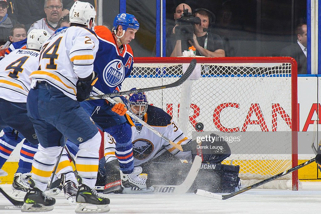 Ryan Smyth #94 of the Edmonton Oilers eyes the loose puck in front of the net of Matt Hackett #31 of the Buffalo Sabres during an NHL game at Rexall Place on March 20, 2014 in Edmonton, Alberta, Canada.