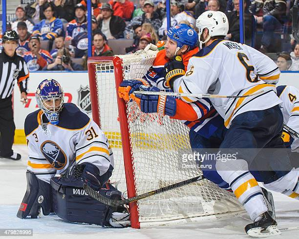 Ryan Smyth of the Edmonton Oilers gets checked by Mike Weber of the Buffalo Sabres in front of the net of Matt Hackett during an NHL game at Rexall...