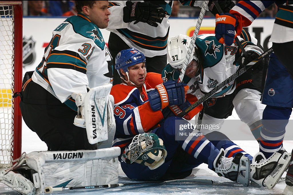 Ryan Smyth #94 of the Edmonton Oilers gets tangled up in front of Antti Niemi #31 as he battles for position with Adam Burish #37 of the San Jose Sharks on March 20, 2013 at Rexall Place in Edmonton, Alberta, Canada.