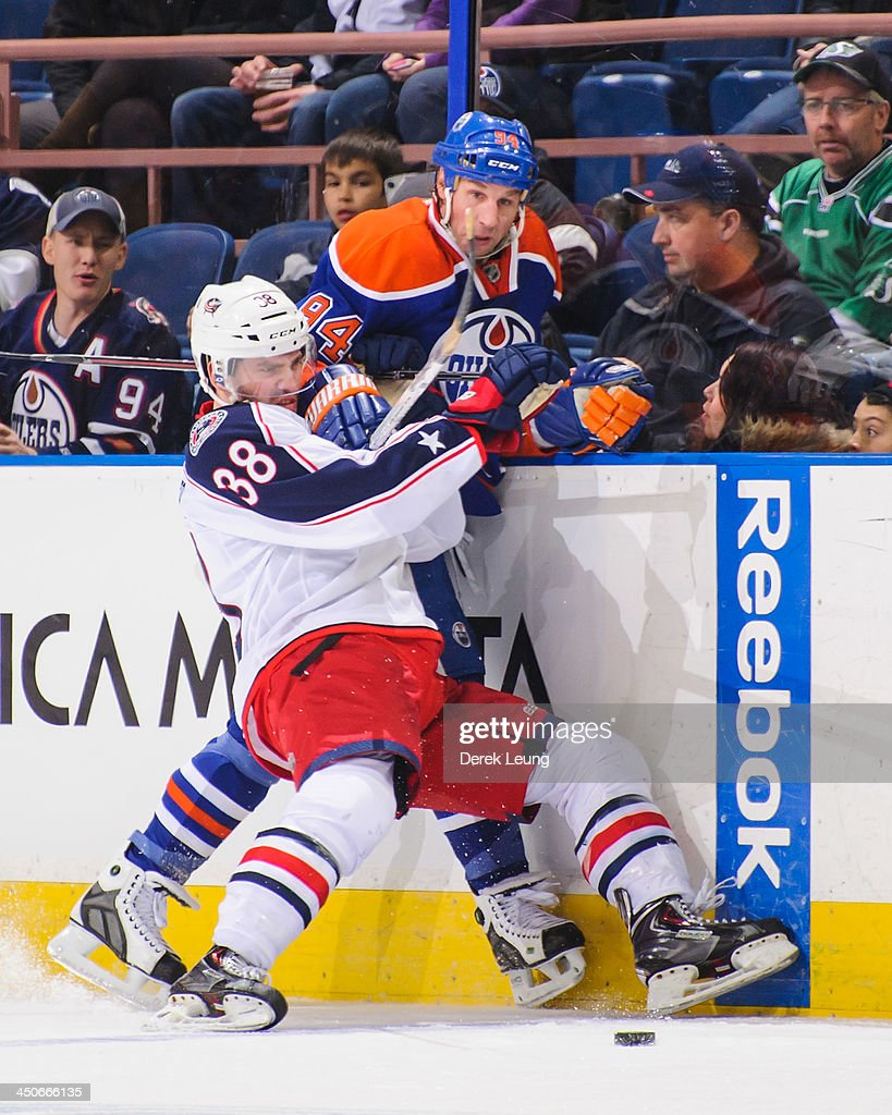 <a gi-track='captionPersonalityLinkClicked' href=/galleries/search?phrase=Ryan+Smyth+-+Ice+Hockey+Player&family=editorial&specificpeople=202567 ng-click='$event.stopPropagation()'>Ryan Smyth</a> #94 of the Edmonton Oilers is checked into the boards by <a gi-track='captionPersonalityLinkClicked' href=/galleries/search?phrase=Boone+Jenner&family=editorial&specificpeople=6480665 ng-click='$event.stopPropagation()'>Boone Jenner</a> #38 of the Columbus Blue Jackets during an NHL game at Rexall Place on November 19, 2013 in Edmonton, Alberta, Canada.