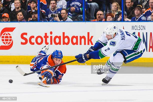 Ryan Smyth of the Edmonton Oilers reaches to check Dan Hamhuis of the Vancouver Canucks during an NHL game at Rexall Place on January 21 2014 in...
