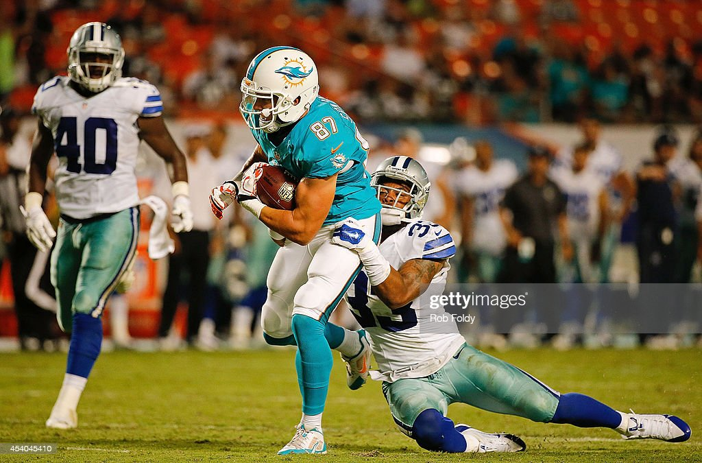 Ryan Spadola #87 of the Miami Dolphins is tackled by Ryan Smith #33 of the Dallas Cowboysduring the game at Sun Life Stadium on August 23, 2014 in Miami Gardens, Florida.