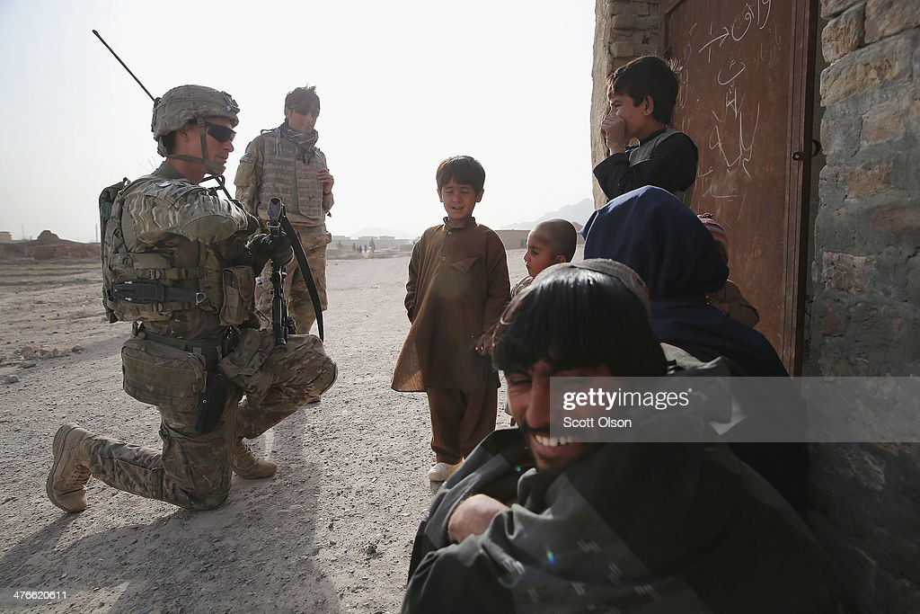 Ryan Spinuzzi-Nichols from Reno, Nevada with the U.S. Army's 4th squadron 2d Cavalry Regiment speaks with residents during a patrol through a village on March 3, 2014 near Kandahar, Afghanistan. President Obama recently ordered the Pentagon to begin contingency planning for a pullout from Afghanistan by the end of 2014 if Afghanistan President Hamid Karzai or his successor refuses to sign the Bilateral Security Agreement.