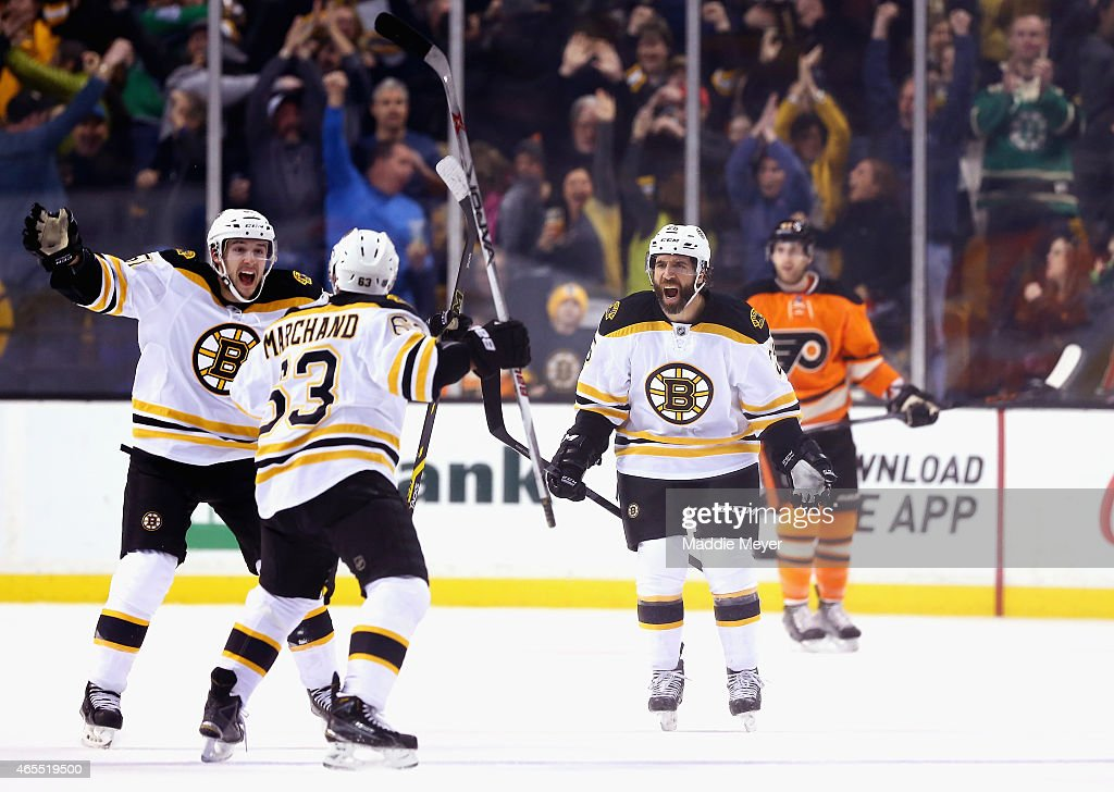 Ryan Spooner and Maxime Talbot congratulate Brad Marchand of the Boston Bruins after he scored the game winning goal in overtime against the...