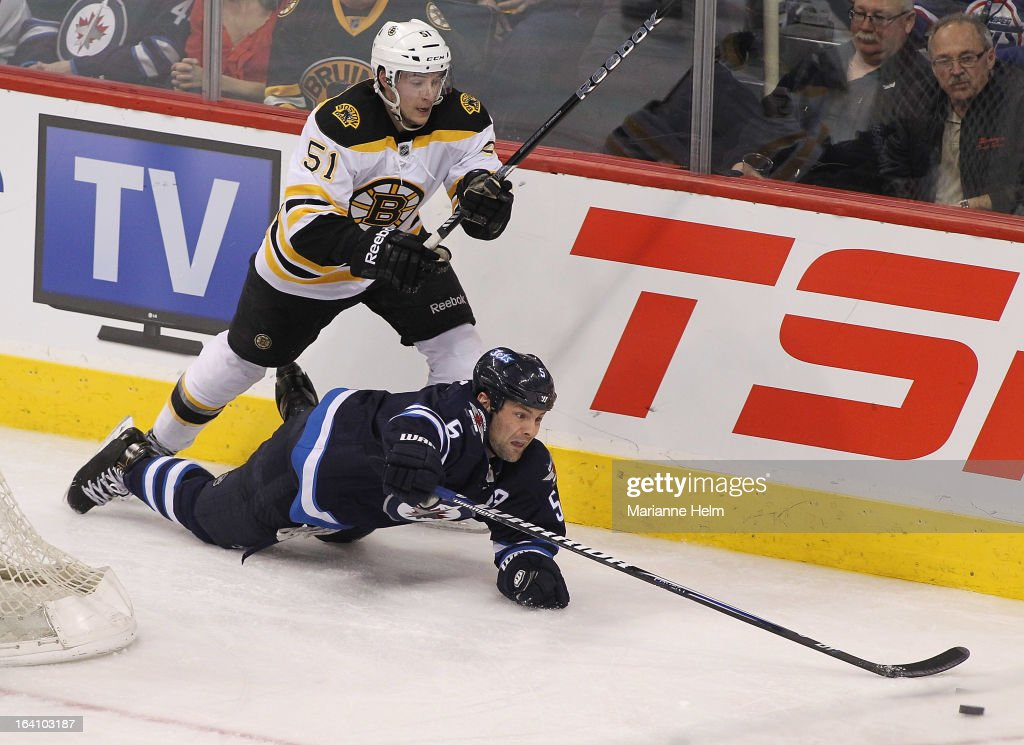 Ryan Spooner #51 of the Boston Bruins and Mark Stuart #5 of the Winnipeg Jets go for the puck during third period action on March 19, 2013 at the MTS Centre in Winnipeg, Manitoba, Canada.