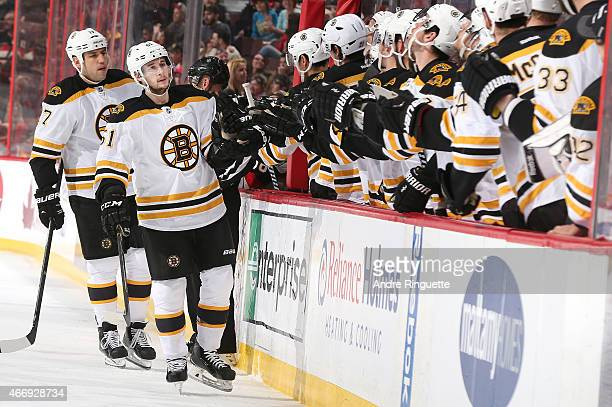 Ryan Spooner of the Boston Bruins celebrates his first period goal against the Ottawa Senators with teammates at the players' bench at Canadian Tire...