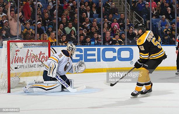 Ryan Spooner of the Boston Bruins scores the gamewinning shootout goal against Chad Johnson the Buffalo Sabres during an NHL game on February 4 2016...