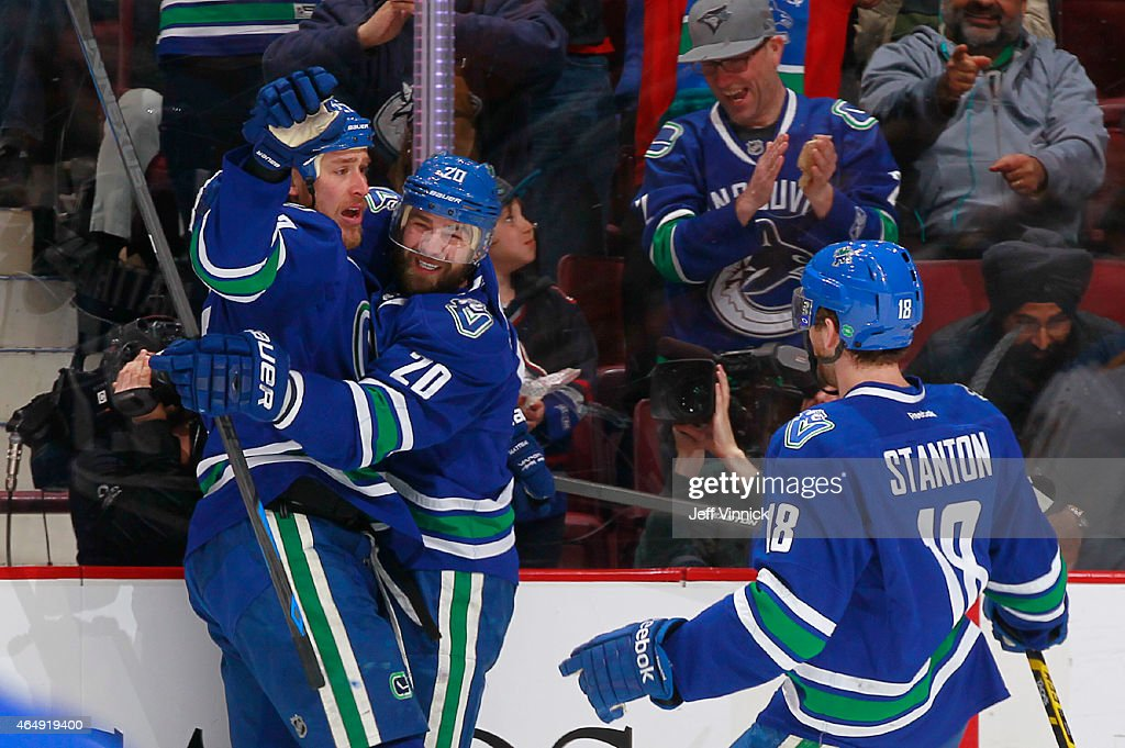 Ryan Stanton and Chris Higgins congratulate Shawn Matthias of the Vancouver Canucks who scored against the St Louis Blues during their NHL game at...