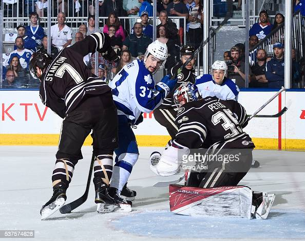 Ryan Stanton and Justin Peters of the Hershey Bears battles for the loose puck with Colin Smith of the Toronto Marlies during AHL Eastern Conference...