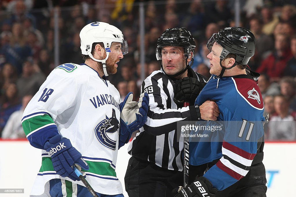 Ryan Stanton of the Vancouver Canucks and Jamie McGinn of the Colorado Avalanche exchange words during the second period at the Pepsi Center on March...