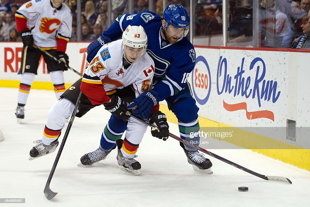 Ryan Stanton #18 of the Vancouver Canucks and Johnny Gaudreau #53 of the Calgary Flames battle for the puck during the third period in NHL action on April 13, 2014 at Rogers Arena in Vancouver, British Columbia, Canada.
