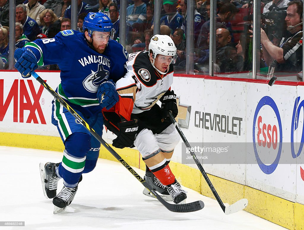 Ryan Stanton of the Vancouver Canucks and Rickard Rakell of the Anaheim Ducks watch a loose puck during their NHL game at Rogers Arena March 9 2015...