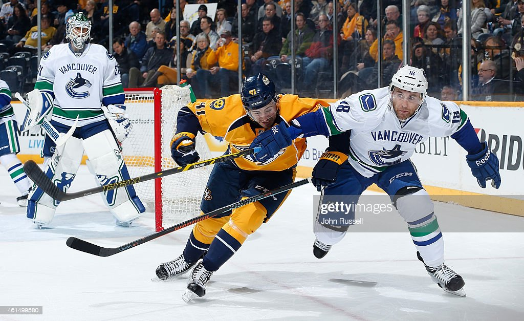 Ryan Stanton of the Vancouver Canucks battles against Taylor Beck of the Nashville Predators during an NHL game at Bridgestone Arena on January 13...