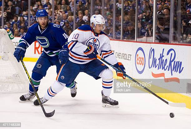 Ryan Stanton of the Vancouver Canucks battles with Nail Yakupov of the Edmonton Oilers for the puck in NHL action on April 2015 at Rogers Arena in...