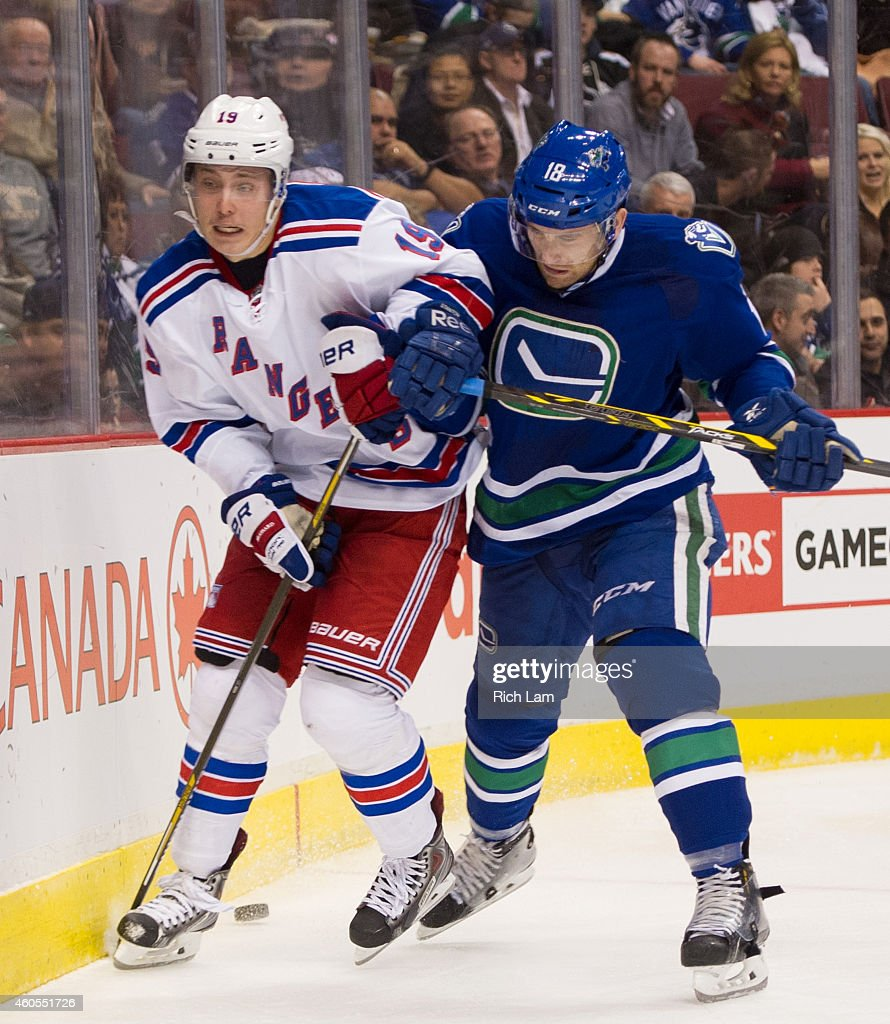 Ryan Stanton of the Vancouver Canucks checks Jesper Fast of the New York Rangers along the end boards during NHL action at Rogers Arena on December...
