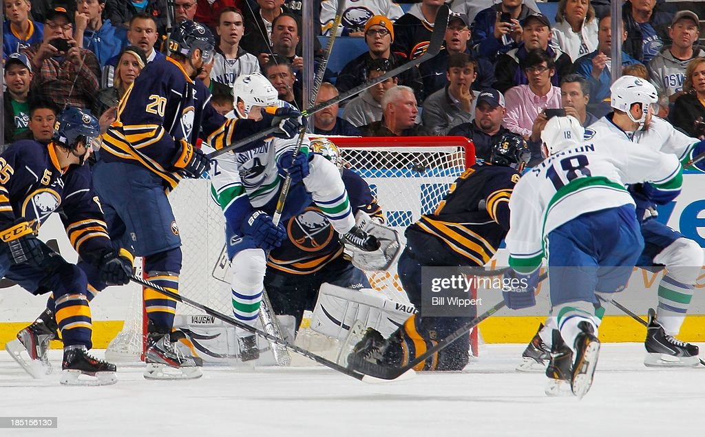 Ryan Stanton #18 of the Vancouver Canucks scores his first career NHL goal over the shoulder of Ryan Miller #30 of the Buffalo Sabres with a screen from Daniel Sedin #22 of the Canucks on October 17, 2013 at the First Niagara Center in Buffalo, New York. Vancouver won, 3-0.