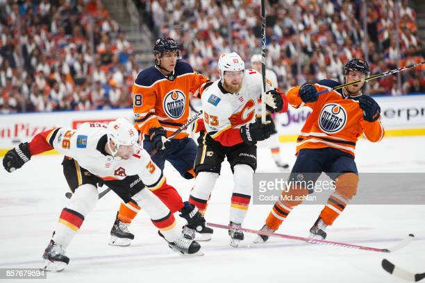 Ryan Strome and Drake Caggiula of the Edmonton Oilers battle against Troy Brouwer and Sam Bennett of the Calgary Flames in the season opener at...