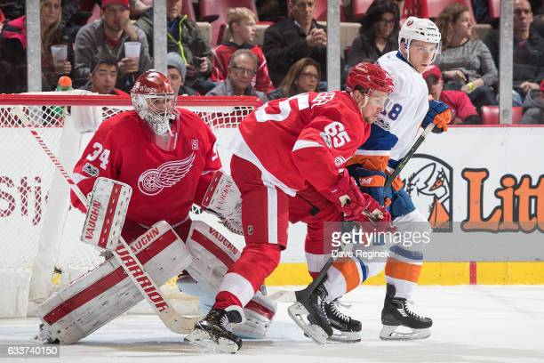 Ryan Strome of the New York Islanders battles for position with Danny DeKeyser of the Detroit Red Wings in front of goaltender Petr Mrazek of the...