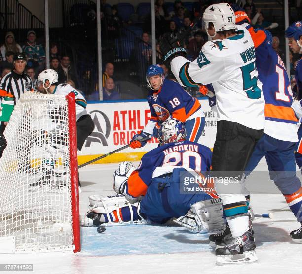Ryan Strome of the New York Islanders watches the puck coming out of the net past goalie Evgeni Nabokov as Jason Demers of the San Jose Sharks skates...