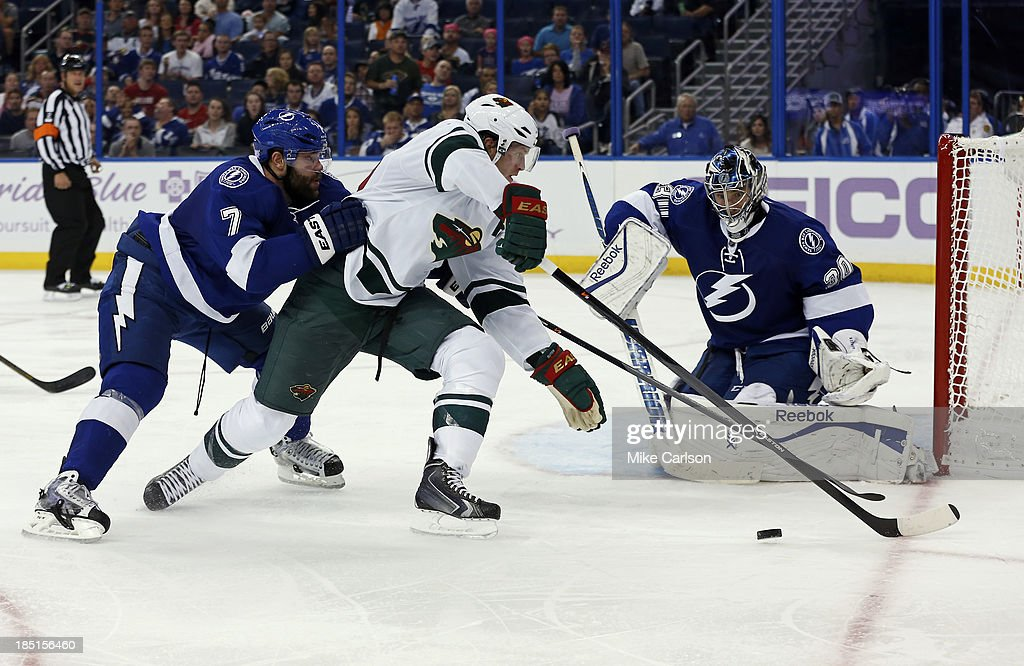 <a gi-track='captionPersonalityLinkClicked' href=/galleries/search?phrase=Ryan+Suter&family=editorial&specificpeople=583306 ng-click='$event.stopPropagation()'>Ryan Suter</a> #20 of the Minnesota Wild (C) avoids the check from <a gi-track='captionPersonalityLinkClicked' href=/galleries/search?phrase=Radko+Gudas&family=editorial&specificpeople=5648763 ng-click='$event.stopPropagation()'>Radko Gudas</a> #7 of the Tampa Bay Lightning in front of goalie <a gi-track='captionPersonalityLinkClicked' href=/galleries/search?phrase=Ben+Bishop&family=editorial&specificpeople=700137 ng-click='$event.stopPropagation()'>Ben Bishop</a> #30 at the Tampa Bay Times Forum on October 17, 2013 in Tampa, Florida.