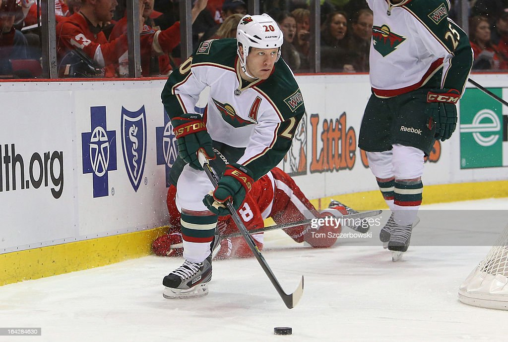 Ryan Suter #20 of the Minnesota Wild picks up the puck during their NHL game against the Detroit Red Wings at Joe Louis Arena on March 20, 2013 in Detroit, Michigan.