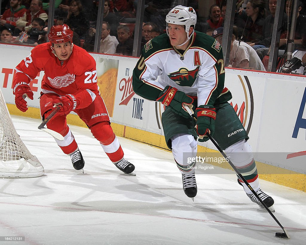 Ryan Suter #20 of the Minnesota Wild skates with the puck as Jordin Tootoo #22 of the Detroit Red Wings pressures him during a NHL game at Joe Louis Arena on March 20, 2013 in Detroit, Michigan.