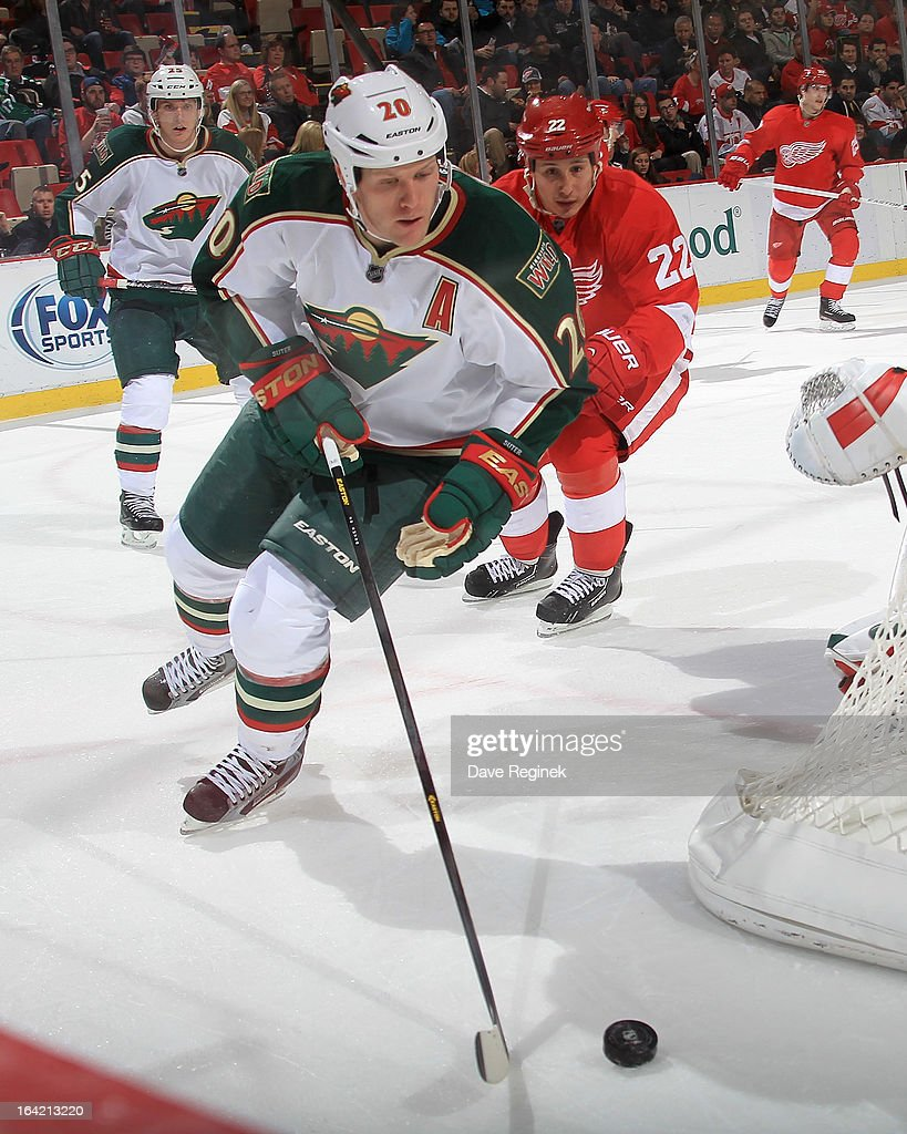 Ryan Suter #20 of the Minnesota Wild skates with the puck as Jordin Tootoo #22 of the Detroit Red Wings pressures him behind the net during a NHL game at Joe Louis Arena on March 20, 2013 in Detroit, Michigan. Minnesota defeated Detroit 4-2