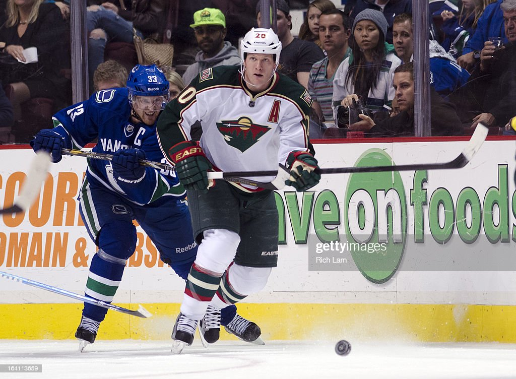 Ryan Suter #20 of the Minnesota Wild skates with the puck while being checked by Henrik Sedin #33 of the Vancouver Canucks during NHL action on March 18, 2013 at Rogers Arena in Vancouver, British Columbia, Canada.