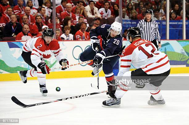 Ryan Suter of the United States passes the puck as Duncan Keith and Jarome Iginla of Canada close in during the ice hockey men's gold medal game...