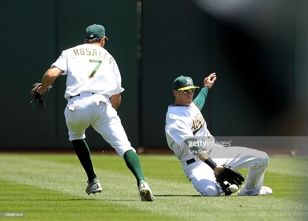 Ryan Sweeney #21 and Adam Rosales #7 of the Oakland Athletics can not catch a ball hit by Miguel Cabrera #24 of the Detroit Tigers in the third inning of their game at the Oakland-Alameda County Coliseum on May 20, 2010 in Oakland, California.