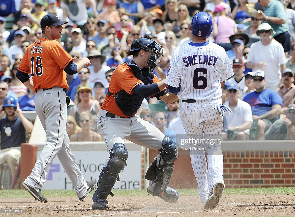 Ryan Sweeney #6 of the Chicago Cubs is tagged out at home plate by Jason Castro #15 of the Houston Astros during the third inning on June 23, 2013 at Wrigley Field in Chicago, Illinois.