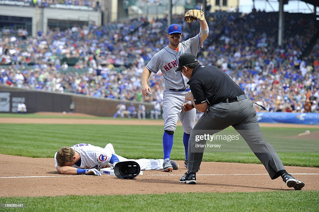 Ryan Sweeney #6 of the Chicago Cubs (L) reacts to the call after third baseman David Wright #5 of the New York Mets (C) tagged him out during the fourth inning on May 19, 2013 at Wrigley Field in Chicago, Illinois. Third base umpire Manny Gonzalez (R) called Sweeney out when he tried to stretch a double into a triple.