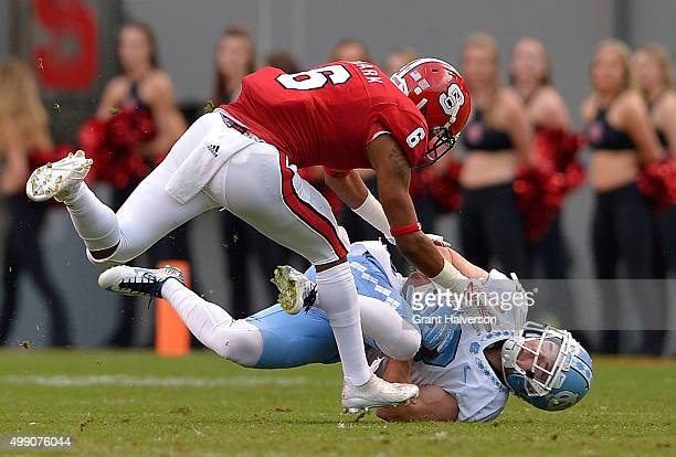 Ryan Switzer of the North Carolina Tar Heels makes a catch against Niles Clark of the North Carolina State Wolfpack during their game at CarterFinley...