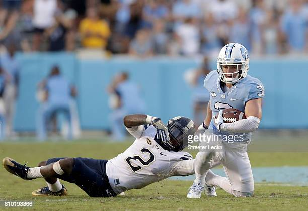 Ryan Switzer of the North Carolina Tar Heels tries to get away from Terrish Webb of the Pittsburgh Panthers during their game at Kenan Stadium on...