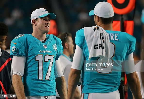 Ryan Tannehill and Matt Moore of the Miami Dolphins talk during a preseason game against the Tampa Bay Buccaneers at Sun Life Stadium on September 3...