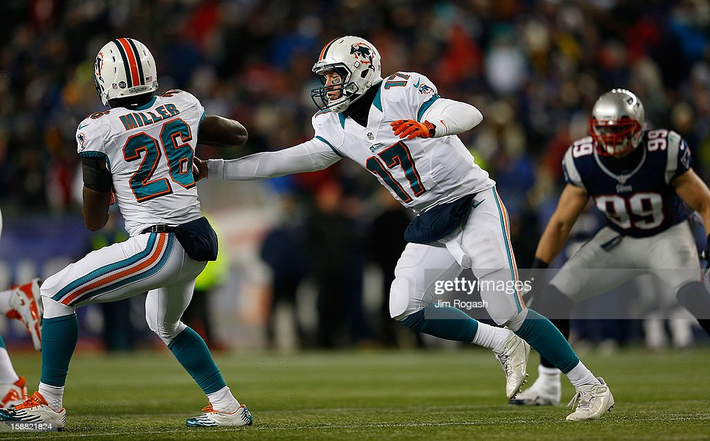 Ryan Tannehill #17 of the Miami Dolphins hands the ball to Lamar Miller#26 in the second half against the Miami Dolphins at Gillette Stadium on December 30, 2012 in Foxboro, Massachusetts.