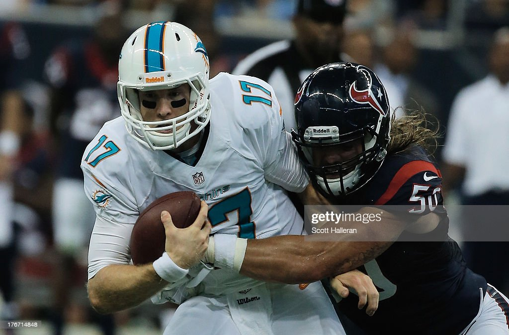 Ryan Tannehill #17 of the Miami Dolphins is sacked by Bryan Braman #50 of the Houston Texans during a preseaon game at Reliant Stadium on August 17, 2013 in Houston, Texas.