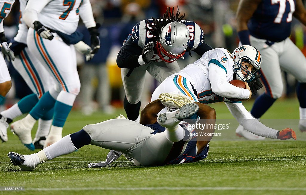 Ryan Tannehill #17 of the Miami Dolphins is sacked by Justin Francis #94 and Jermaine Cunningham #96 of the New England Patriots in the second half during the game at Gillette Stadium on December 30, 2012 in Foxboro, Massachusetts.