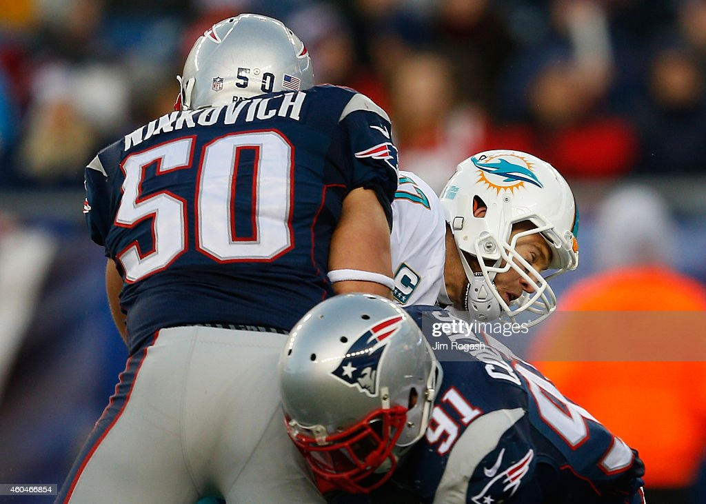 Ryan Tannehill of the Miami Dolphins is sacked by Rob Ninkovich of the New England Patriots during the fourth quarter at Gillette Stadium on December...